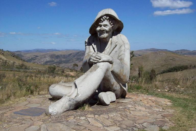 Estátua de um homem sentado, com chapéu, e a serra ao fundo