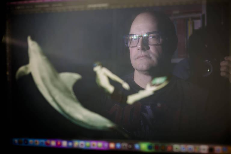 imagem de um homem branco de óculos refletida na tela do computador