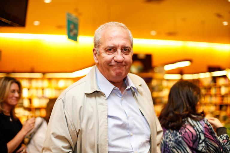 Homem sorridente, de cabelos ralos e brancos, vestido com camisa branca e jaqueta bege, numa livraria. Atrás dele, estantes de livros e frequentadores da livraria conversando.