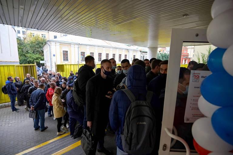 Russos fazem fila do lado de fora de uma seção eleitoral para votar no primeiro dia da eleição parlamentar de três dias em Moscou