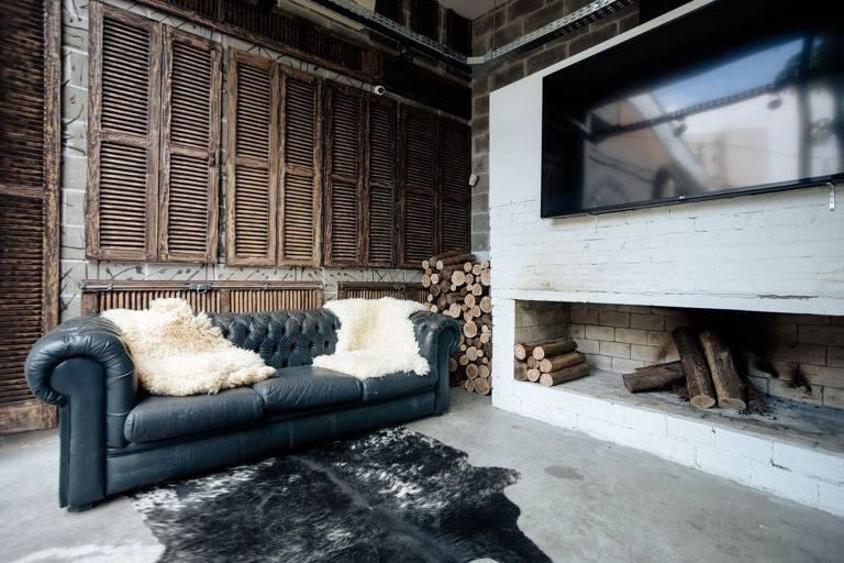 Sala com sofá com mantas de pele em cima dele, tapete de pele, televisão e local que armazena madeira para ladeira