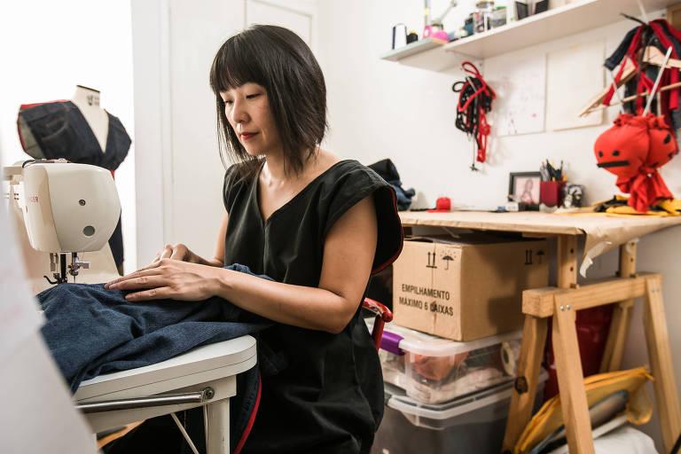 Luci usa a máquina de costura em seu ateliê