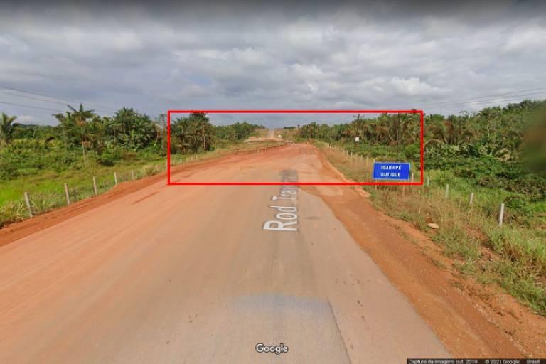 Estrada com céu azul com nuvens ao fundo e mato nas margens direita e esquerda