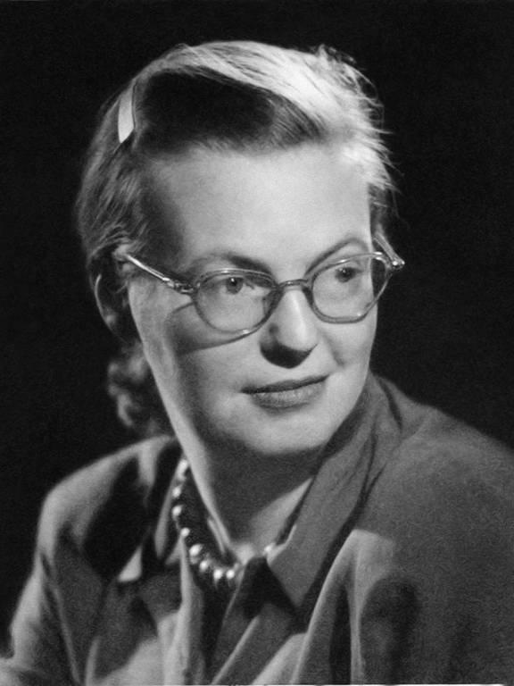 mulher branca de cabelos presos e óculos
