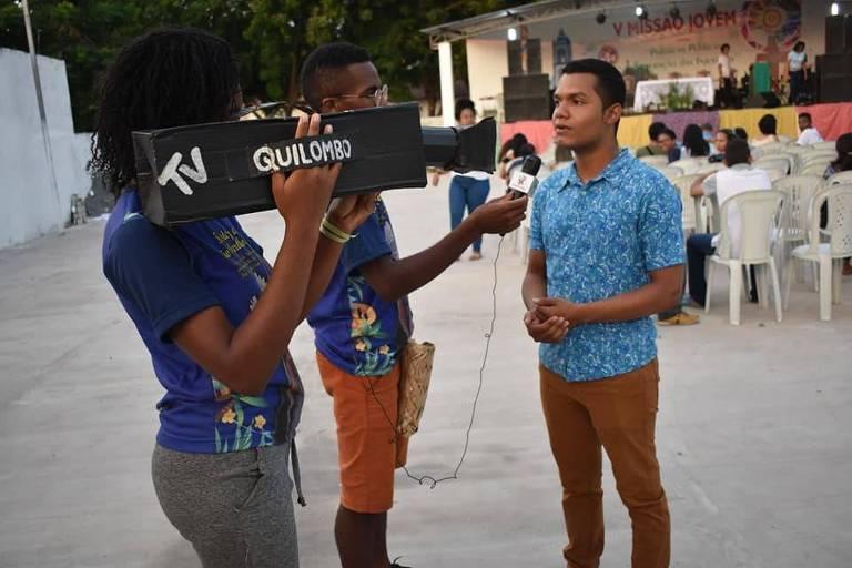 Repórter com microfone e menina com câmera entrevistam uma pessoa
