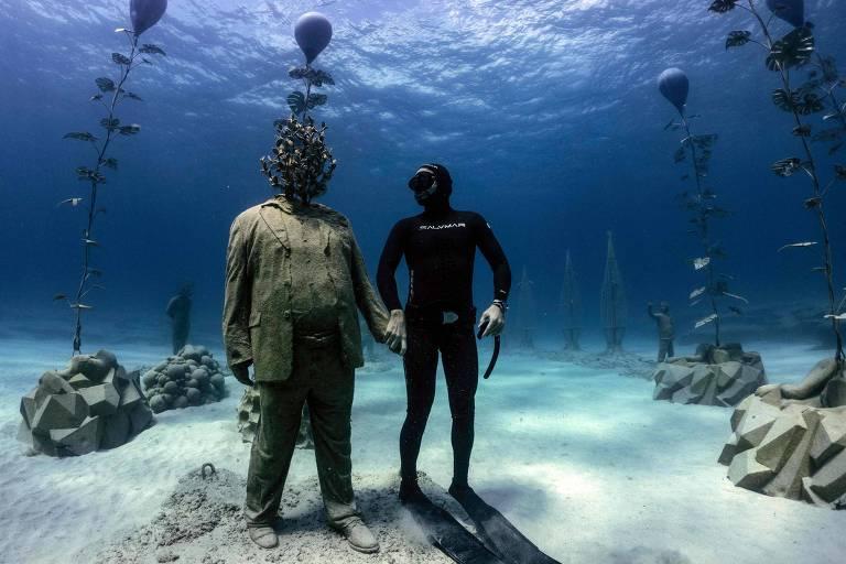 Mergulhador posa com uma estátua no parque de esculturas subaquáticas do Chipre