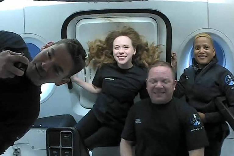 Quatro pessoas vestindo camisetas pretas sorriem dentro de uma nave com paredes brancas