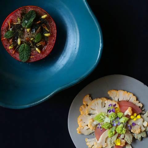 Couve-flor, crua e marinada, com alface-do-mar, uma alga e tomate morno cozido lentamente com morango e nêspera lactofermentados, hortelã e sal (à esq.)