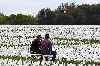 People sit among white flags near the Washington Monument in Washington on Sept. 17, 2021, that are part of artist Suzanne Brennan Firstenberg's temporary art installation,