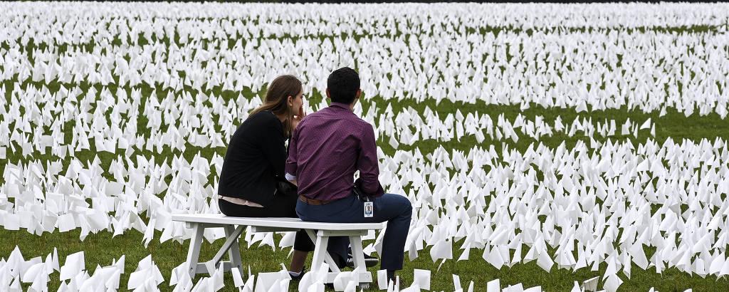 Visitantes em meio a bandeiras brancas que representam vítimas da Covid nos EUA, instaladas no National Mall, em Washington