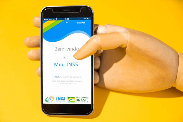 Mão de madeira segura celular com o aplicativo Meu INSS.
