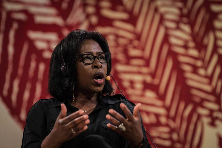 Mulher negra fala em microfone gesticulando com as duas mãos