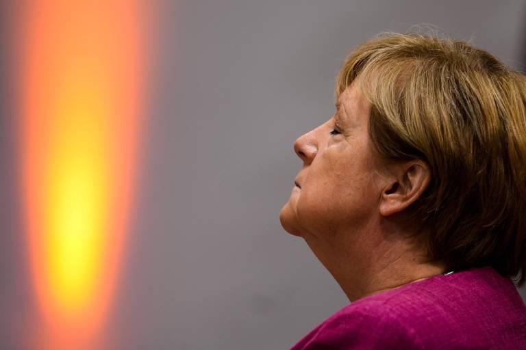 Perfil esquerdo de Merkel, de olhos fechados e queixo levemente erguido, ocupa canto direito da foto; no canto esquerdo, um faixo de luz parece uma chama gigante de uma vela. Merkel veste um paletó grená