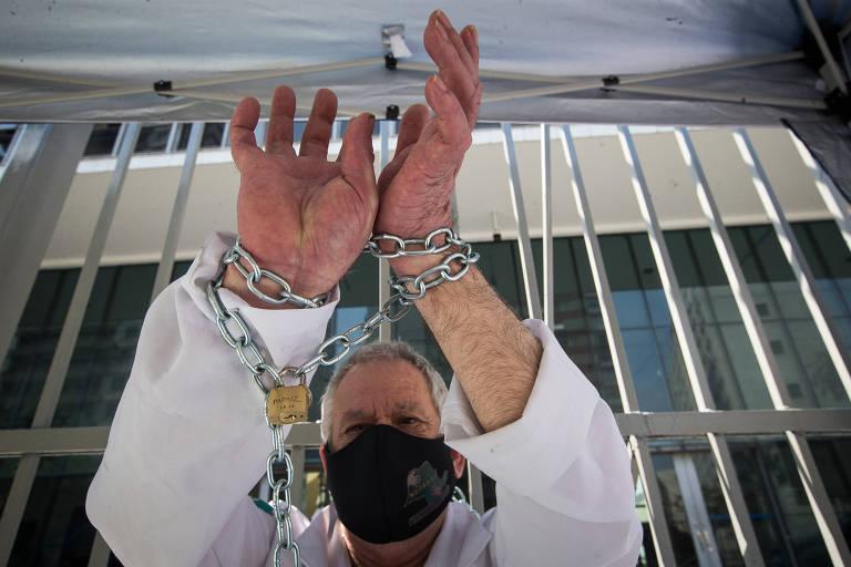 Homem com máscara preta mostra correntes presas entre suas mãos e o portão da Câmara Municipal