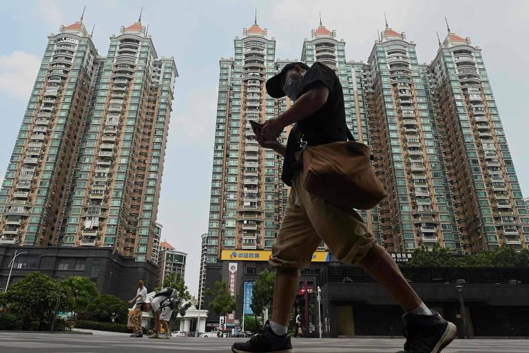 Homem caminha diante de complexo habitacional da Evergrande em Guangzhou, na China