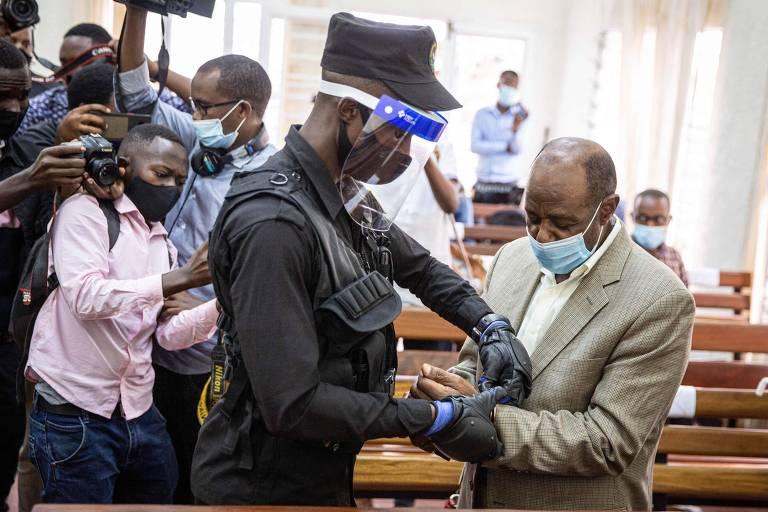 Paul Rusesabagina é algemado por um policial, após sua sessão de pré-julgamento no tribunal primário de Kicukiro, em Kigali, Ruanda