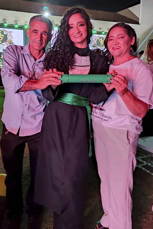 Nilcinádia está no centro da foto vestindo uma beca e segurando o canudo com seu diploma, seus pais seguram o diploma com ela, um de cada lado