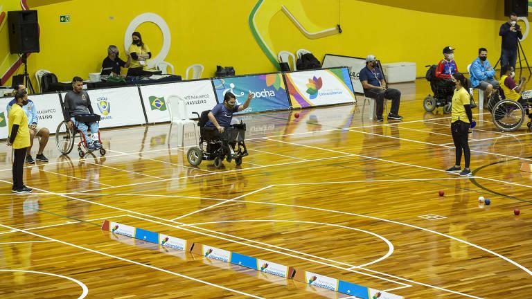 Atletas jogam bocha em uma quadra de piso de madeira e parede amarela