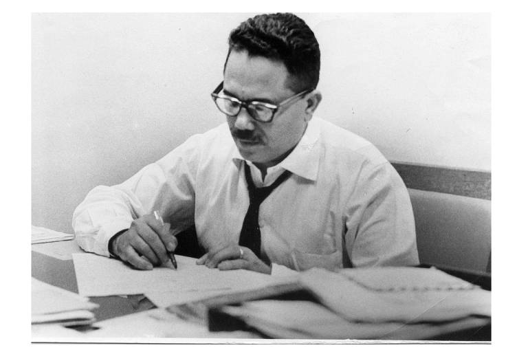 retrato em preto e branco de homem sentado em uma mesa escrevendo em um papel