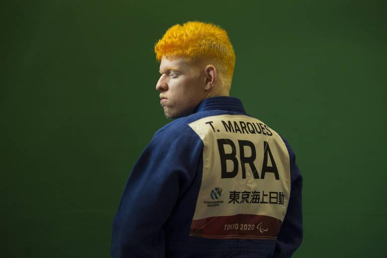 Thiego é um homem albino, com cabelos pintados de laranja; está em uma sala com parede verde, mostrando as costas do quimono azul, onde está a identificação de seu nome e da seleção brasileira, há alguns ideogramas em japonês na roupa, identificando a participação nas Paralimpíadas de Tóquio