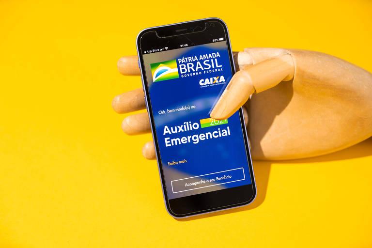 Foto mostra um fundo amarelo com uma mão articulada de madeira segurando um celular, onde uma tela azul do aplicativo do auxílio emergencial está aberta.