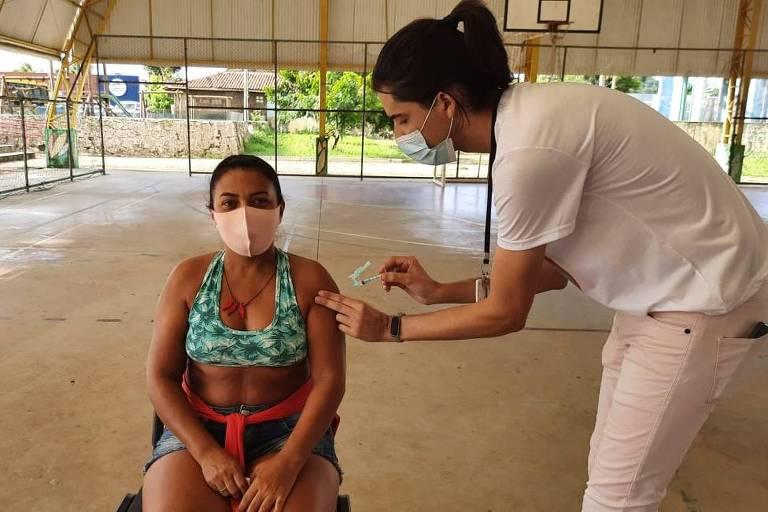 mulher com máscara é vacinada por funcionária da saúde