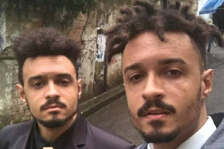 Dois homens negros vestindo ternos posando para selfie em uma rua
