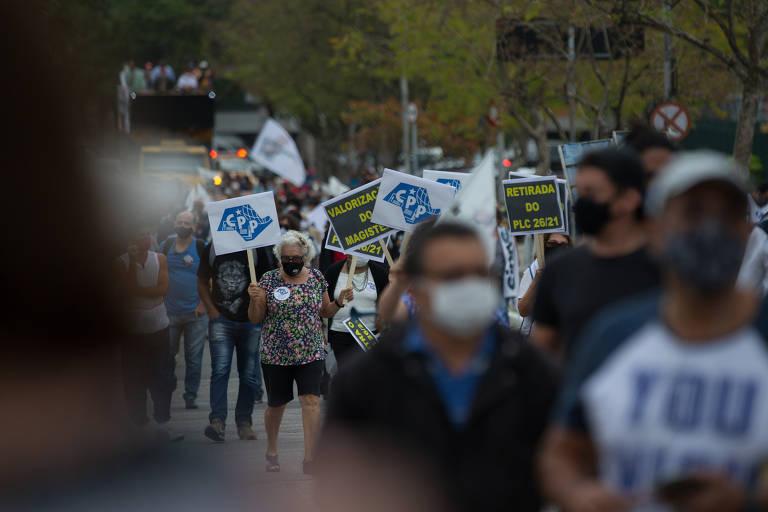 Foto mostra várias pessoas caminhando em uma rua arborizada. Há placas com os dizeres CPP e é possível ver um caminhão de som ao fundo.