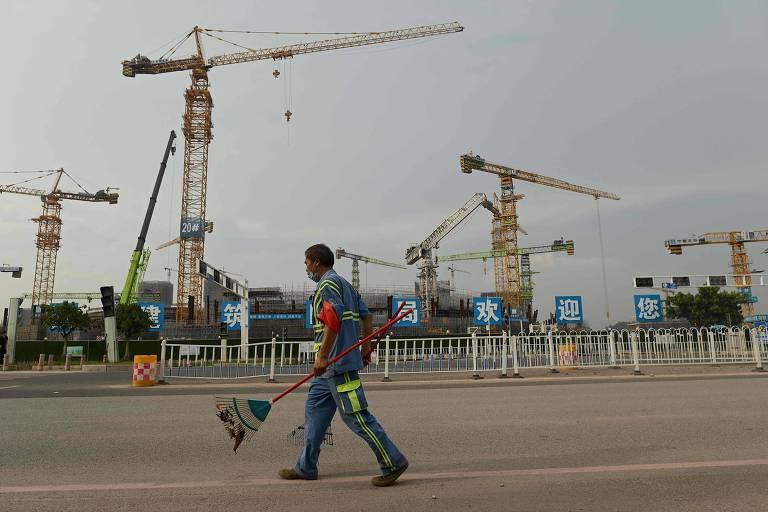 Trabalhador diante do canteiro de obras do estádio do time de futebol Guangzhou Evergrande, em Guangzhou, na China