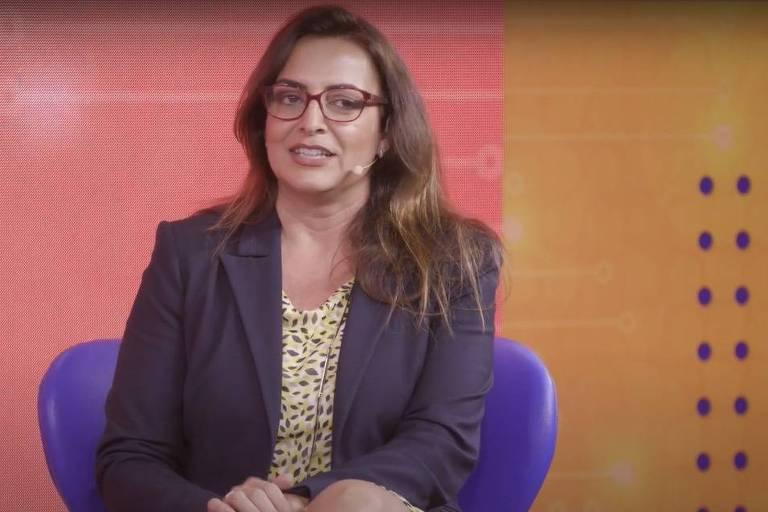 Palestrante Catherine Moura, sentada em uma cadeira, fala durante 8º Congresso Todos Juntos Contra o Câncer