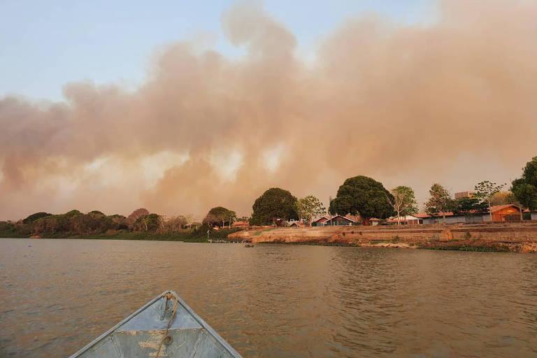fumaça rosada sobe por um céu azul claro à margem de um rio cercado de algumas árvores. em primeiro plano, vemos a ponta de um barco e a água marrom do rio. a foto provavelmente foi tirada por alguém estava nesse barco.