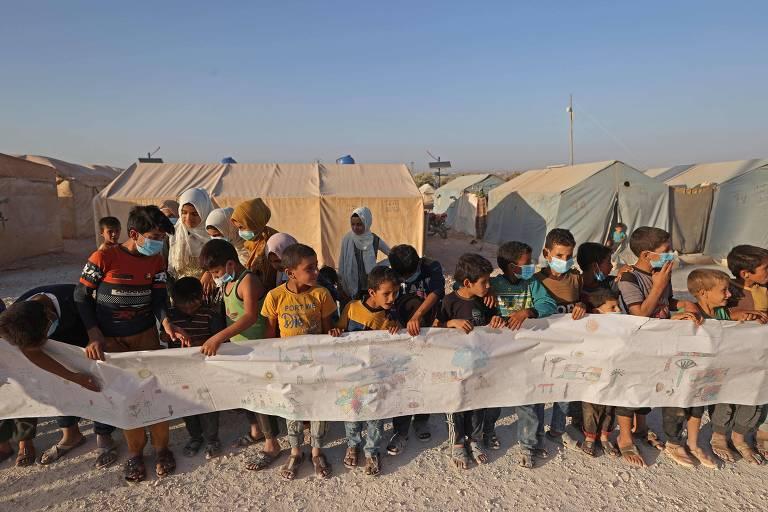 Crianças seguram faixa de papel com desenhos