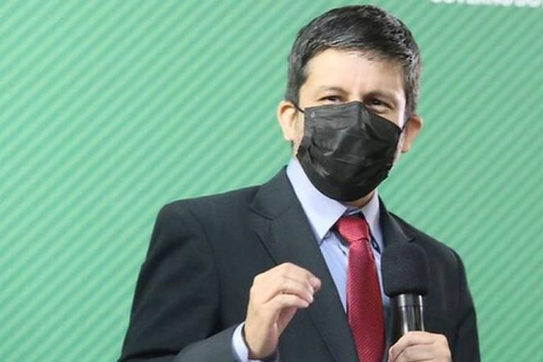 Imagem em primeiro plano mostra Ricardo Palacios de social, máscara e segurando um microfone
