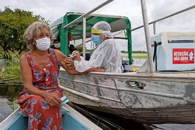 Idosa de máscara recebe vacina de um profissional da saúde. Ela está sentada em um barco e o profissional em outro