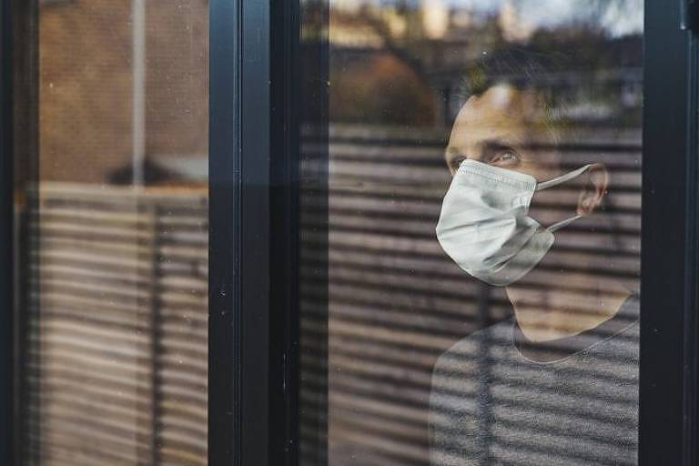 Um homem de máscara está atrás de uma janela de vidro olhando para alto