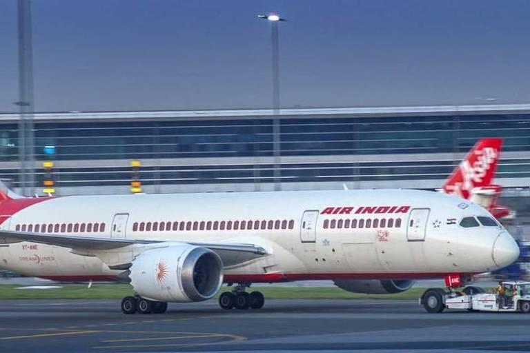 Avião branco com detalhes em vermelho escrito Air India