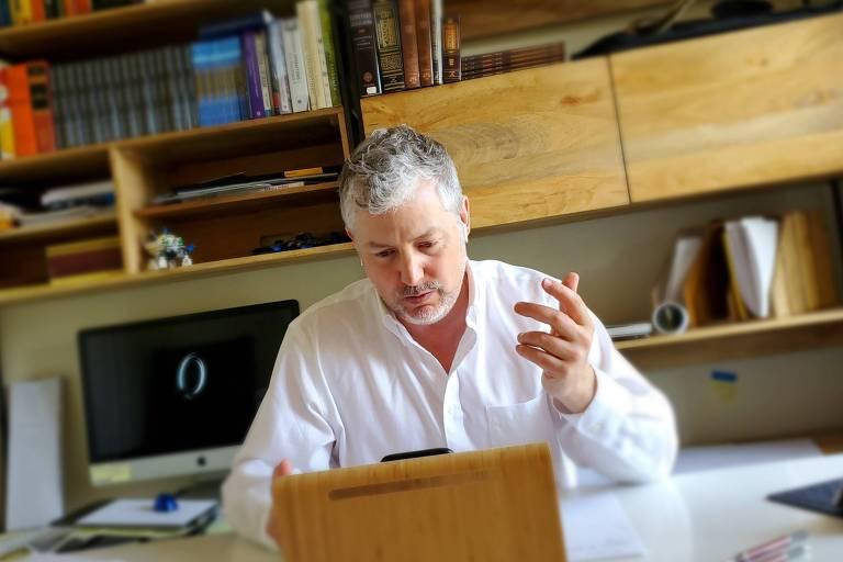 Joshua, um homem branco e cabelos grisalhos, que está sentado diante de uma estante com livros e um computador ao fundo. Ele veste uma camisa branca de mangas longas e gesticula com ma mão esquerda diante de um celular apoiado na mesa