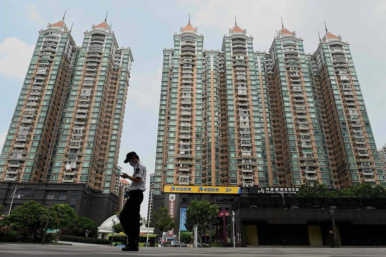 Homem passa diante de um dos complexos residenciais desenvolvidos pela Evergrande na China