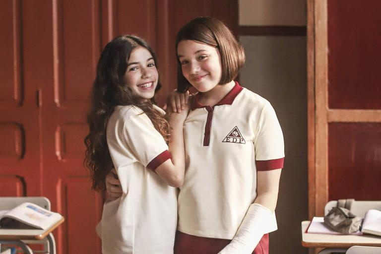 Duas meninas abraçadas em uma sala de aula vestindo uniforme de saia vinho e camiseta polo branca com detalhes em vinho