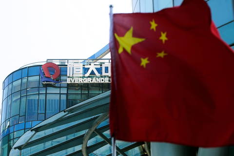 A Chinese flag flutters in front of the logo of China Evergrande Group seen on the Evergrande Center in Shanghai, China September 22, 2021. REUTERS/Aly Song REFILE - QUALITY REPEAT ORG XMIT: PPPALY02