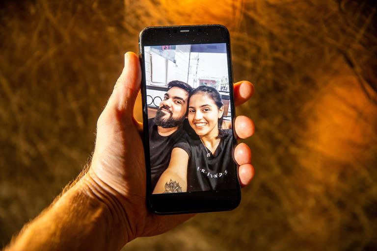 Casal é visto em foto em tela de telefone com fundo âmbar
