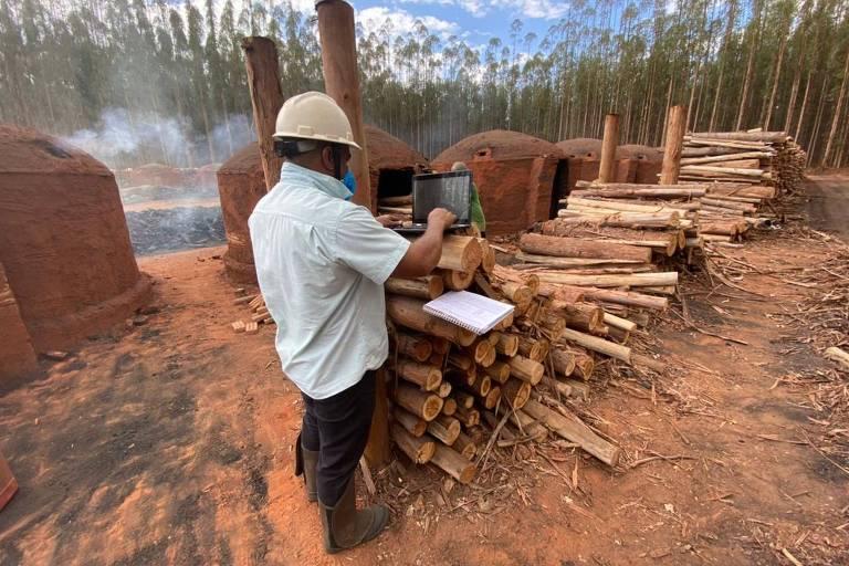 Engenheiro opera equipamento de controle de temperatura de forno para produção de carvão vegetal em Andrelândia (MG)