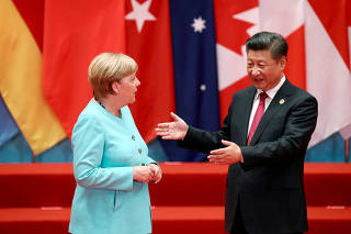 FILE PHOTO: Chinese President Xi Jinping talks with German Chancellor Angela Merkel as they pose for a group picture during the G20 Summit in Hangzhou