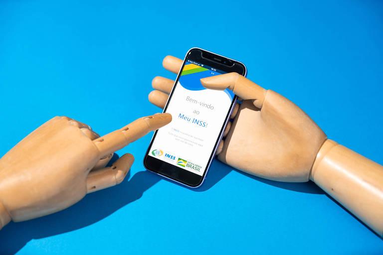 Mão de madeira segura celular que exibe a tela do aplicativo Meu INSS