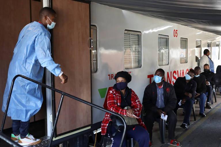 Profissional de saúde conversa com pessoas que esperam para receber vacina em um trem na África do Sul