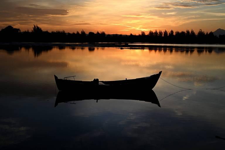 Barco em lago enquanto horizonte se ilumina
