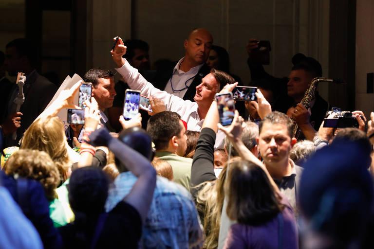 O presidente Jair Bolsonaro cumprimenta apoiadores ao sair do hotel em que estava hospedado em Nova York