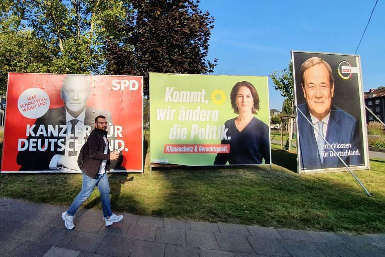 Homem passa em frente a outdoors com fotos de candidatos