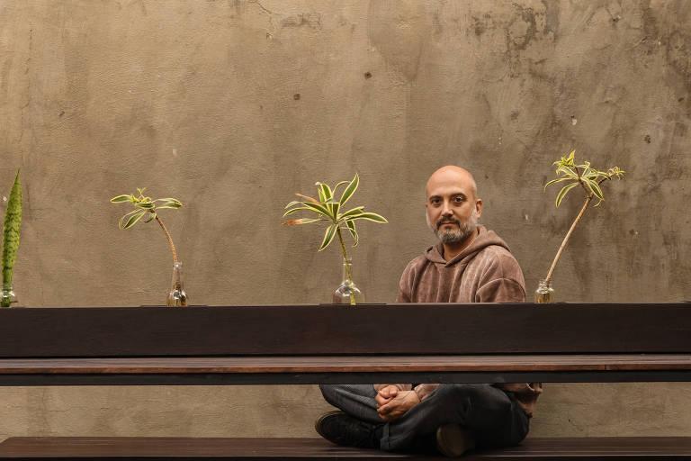 Rogerio está sentando com as pernas cruzadas em meio a mudas de plantas