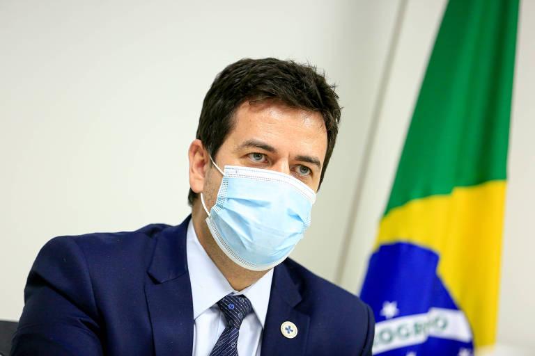 Rodrigo Cruz, o secretário-executivo do Ministério da Saúde, de terno azul e máscara, com a bandeira do Brasil ao fundo
